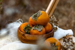 Sweet delicious persimmon, on a wooden stool, outdoors in the open air, against the background of an autumn landscape, beautiful colors, an interesting picture and seasonal orange fruits