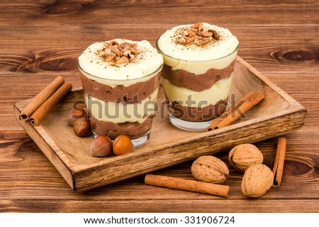 Sweet dessert - chocolate and vanilla pudding in glasses served on the wooden tray with nuts and  cinnamon sticks.