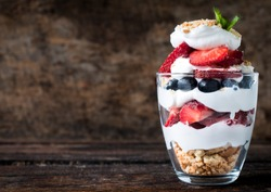 Sweet dessert in glass with biscuit,berry fruit and whipped cream,selective focus and blank space