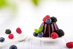 Sweet dessert jelly pudding with berries raspberries blackberries blueberries on white plate