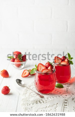 Sweet dessert jelly pudding with strawberries in glass jar on white background Stock photo ©