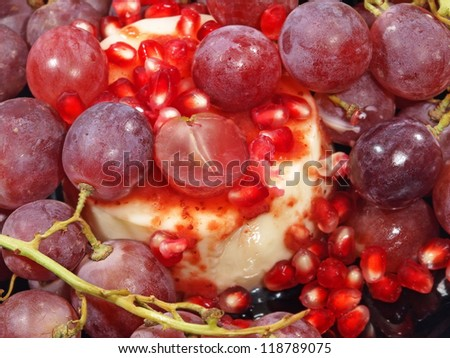 Sweet dessert with fresh grapes berries and pomegranate grains taken closeup.