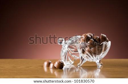 Sweet desserts, closeup shot of chocolate bonbons in elegant glass bowl.