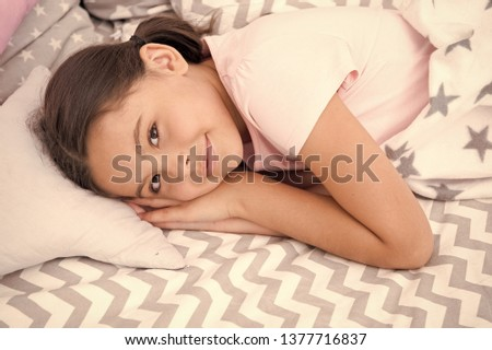 Sweet dreams. Girl smiling happy child lay on bed with star pattern pillows and cute plaid in her bedroom. Bedclothes for children. Modern fashionable bedclothes. Girl kid waking up in morning.
