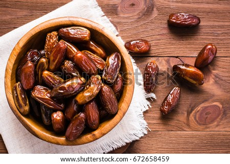 Sweet dried dates fruit in a wooden bowl and on the table. Top view #672658459