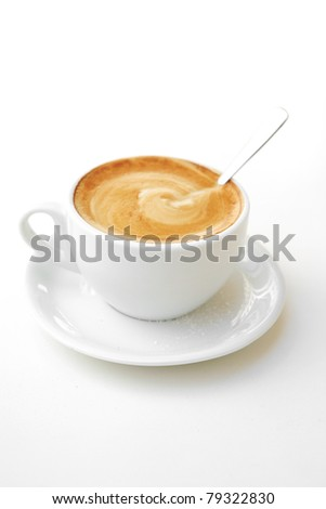 sweet drink : small white cup of cappuccino coffee on light background with spoon