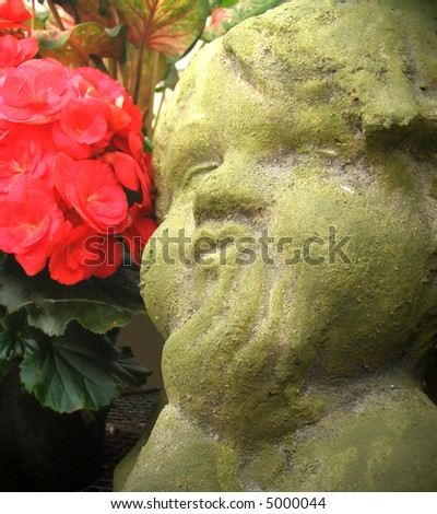 Sweet-faced cherub in a begonia garden - stock photo