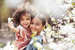 Sweet family portrait of two little sisters outdoors in springtime