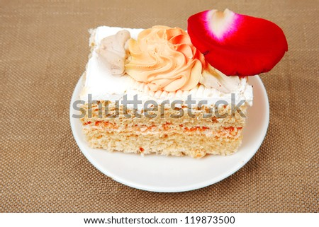 sweet food: cake with whipped cream served with roses on white saucer
