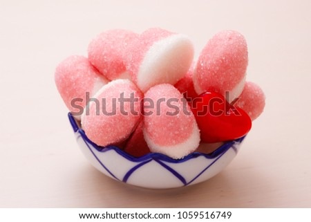 Sweet food candy. Pink jellies or marshmallows with sugar in bowl on wooden table decorated with red heart love symbol #1059516749