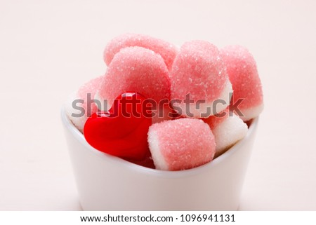 Sweet food candy. Pink jellies or marshmallows with sugar in white bowl on wooden table decorated with red heart love symbol #1096941131
