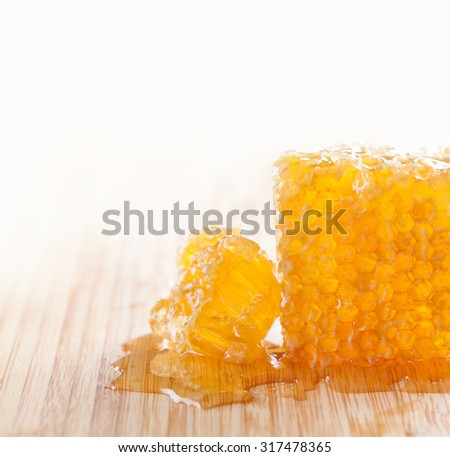 Sweet food concept. tasty honeycomb on the wooden table. White background. Tasty, sticky gold honey combs texture with fresh honey. macro view. soft focus. copy space
