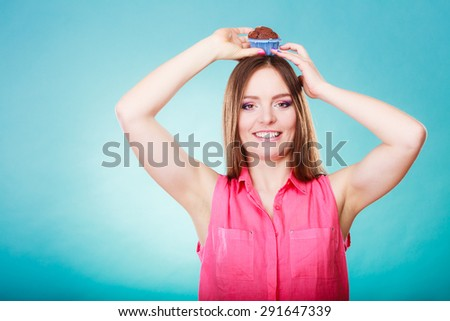 Sweet food sugar make us happy. Smiling crazy woman holds cake chocolate muffin on head blue background