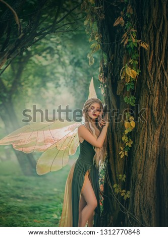 sweet forest angel, nymph with perfect thick white hair in image of dreamy spirit with butterfly wings. attractive fairy with bare legs, mythical creature closes eyes, listens to breath of nature. #1312770848