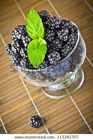 Sweet fresh fruits in glass goblet with mint leaf