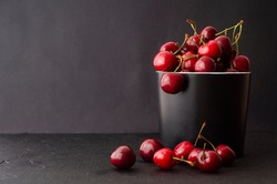 Sweet fresh red cherries in ceramic bowl on black stone background. Fruits healthy food. Black background with space for text
