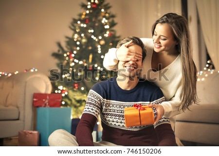 Sweet girl giving a Christmas gift to her boyfriend #746150206