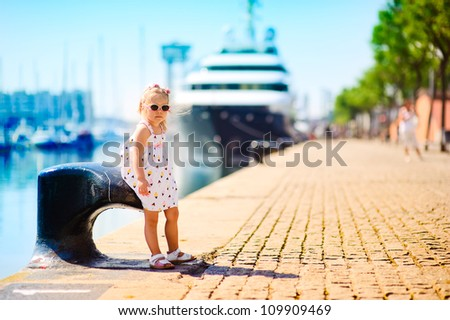 sweet girl in a dock, big cruise ship on background