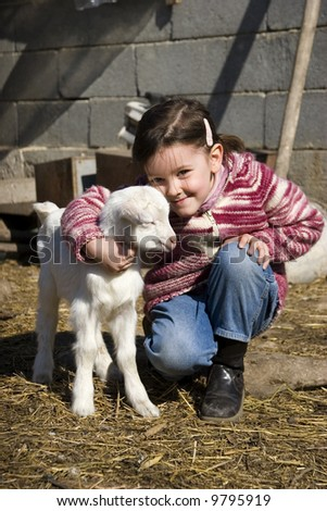 Sweet girl with new born goat in th e farm