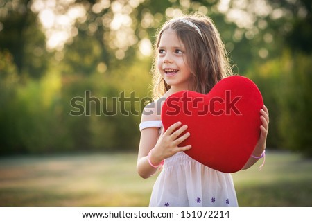 Sweet girl with red heart outdoors in the park