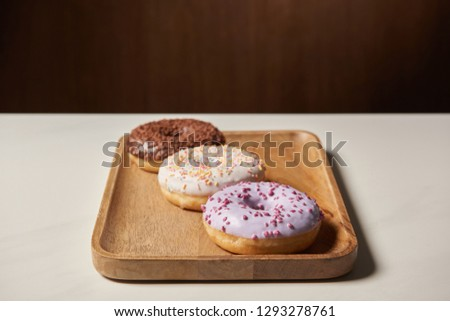 sweet glazed doughnuts with sprinkles on wooden cutting board #1293278761