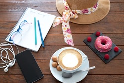 Sweet goodmorning on a wooden table prepared with an  hot cappuccino and a pink donut with some raspberries.  Cellphone and a notepad