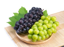 Sweet Green grape and Black grape in Bamboo basket isolated on white background, Shine Muscat Grape and Kyoho Grape with leaves isolated on white
