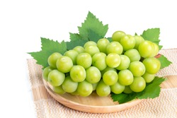 Sweet Green grape on wooden plate isolated on white. Shine Muscat Grape with leaves on white.
