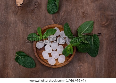 Sweet hard peppermint candy and leaves of fresh mint