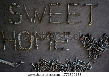 Sweet home industrial style sign. Words made of old bolts. Grey concrete bakcground.
