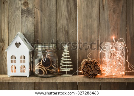 Sweet home. White Christmas decor on vintage natural wooden background. Cinnamon sticks and dried citrus. Cafe shelf.