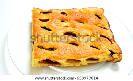sweet homemade cake with fruit fresh plumps and texture-baked dough cut into square against clear glass plate. Peace of home holiday cake as best addition to a cup of coffee or tea