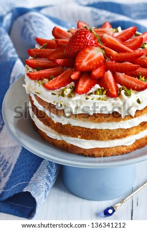 Sweet homemade cake with strawberry and whipped cream on a cake stand