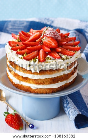 Sweet homemade cake with strawberry and whipped cream on a cake stand. - stock photo