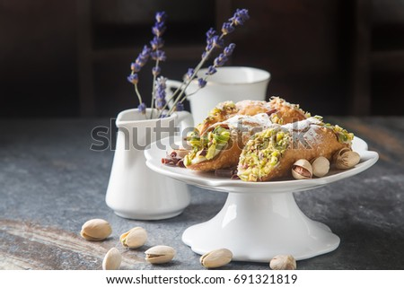 Sweet homemade cannoli stuffed with ricotta cheese cream and pistachios. Traditional Sicilian dessert. Italian pastry. selective focus. Lavender. Dark background