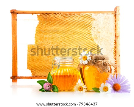 sweet honey in glass jars and honeycomb with  flowers isolated on white background