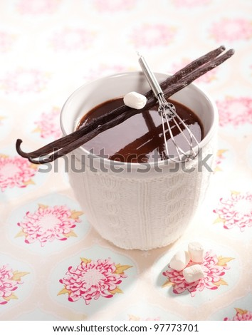 Sweet hot Cacao with Marshmallows and vanilla sticks on a decorative background.