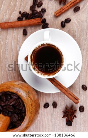sweet hot drink : black arabic coffee in small white cup with mortar and pestle , beans spilled over wooden table , decorated with cinnamon sticks and anise stars