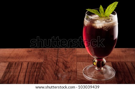 sweet iced tea on a bar top isolated on a black background garnished with fresh mint