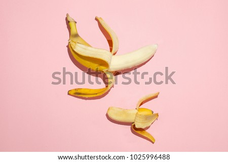 Sweet juicy opened small banana and opened big banana on pink table. Comparing sizes. Sexual life libido, penis size and potency concept.