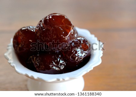 Sweet Jujube or Chinese red date in syrup in white Thai style cup on wood table and space for write wording, Clever idea for fresh fruit preservation, popular sweet, unhealthy food cause of disease #1361188340