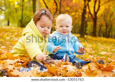 Sweet kids sitting on the autumn leaves