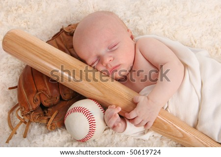 Sweet Little Baby Boy Holding a Baseball Bat With Glove and Ball
