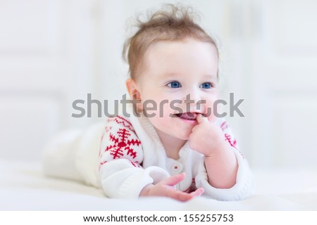 Sweet little baby wearing a knitted sweater with red Christmas ornament