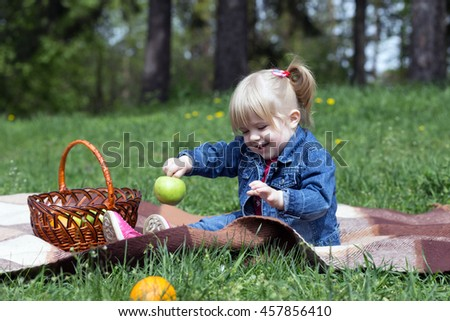 Sweet little blond girl child with blue eyes playing outdoors with curly hair in the wind on a family picnic.