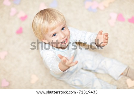 Sweet little boy sitting on the floor in pajamas and stretching his hands. There are little heart shapes around him.