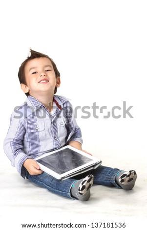 Sweet little boy sitting using a digital tablet.