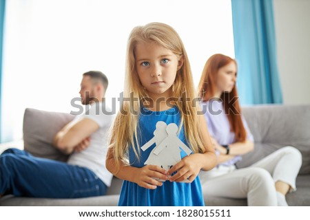 sweet little caucasian child girl holding family picture drawing feeling upset about parents divorce, innocent sensitive little kid suffer from trauma offended by fights conflicts shared custody