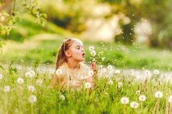 Sweet little girl blowing dandelion sitting between dandelions