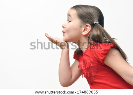 Stock Photo Sweet little girl blowing kisses, wearing a red t-shirt with hearts.